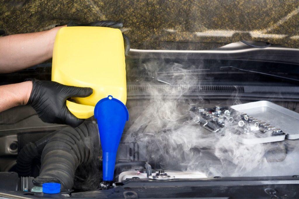 煙が出ているエンジンにオイル補充をする人