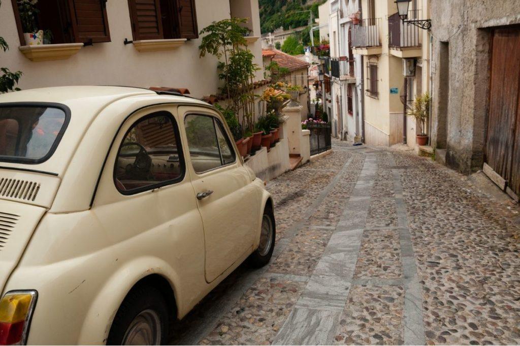 狭い坂道に駐車した白い車