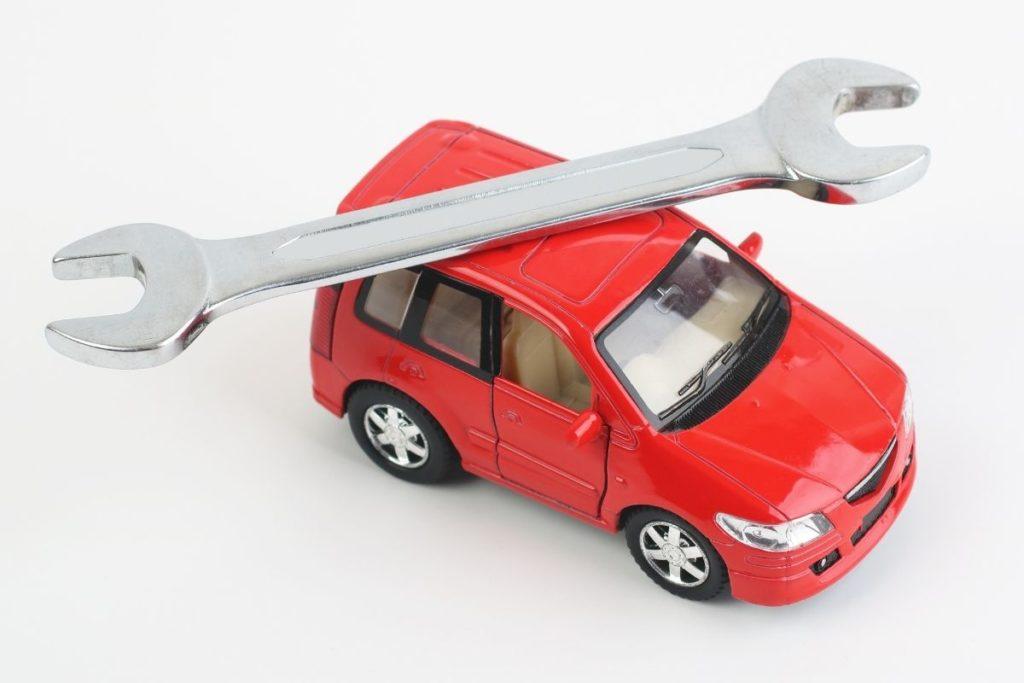 赤い車の上にあるスパナ